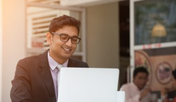 indian business male having coffee at cafe while working
